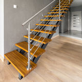 Wooden stairs with silver railing Stock Photo