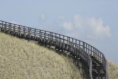 Wooden stairway in the dunes, Petten, Netherlands. A wooden stairway in the dunes in Petten, The Netherlands. This stairway leads to a viewing point from which Royalty Free Stock Photo