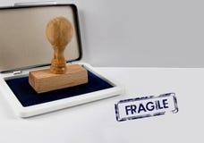 Wooden stamp FRAGILE. Wooden stamp on a desk FRAGILE Stock Image