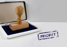 Wooden stamp PRIORITY Stock Images