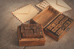 Wooden stamps alphabet and vintage envelopes Royalty Free Stock Images