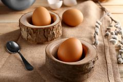 Wooden stands with Ester eggs. On linen tablecloth Stock Photos
