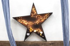 Wooden star with christmas lights on wood background. Star with lights on a white background. Wooden star with christmas lights on wood background. Star with Stock Images
