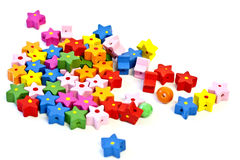 Wooden stars. Painted wooden star beads of different colors, with one round bead Royalty Free Stock Images