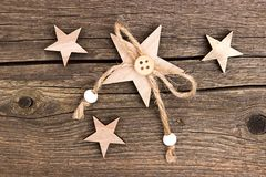 Wooden stars with string on wood. Wooden stars with a string of pearls and a button on a wooden background stock images