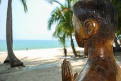 Wooden statue of an asian girl on the beach. The statue shows a greeting royalty free stock photography