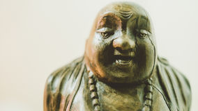 Wooden statue laughing Buddha. The character of Chinese Buddhism. Unfocused Royalty Free Stock Image