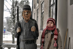 Wooden statue of a soldier and tourist girl Stock Image