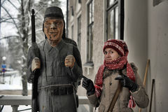 Wooden statue of a soldier and tourist girl Stock Photos