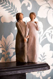 Wooden statue of two women holding hands, statue is on a black  Royalty Free Stock Photos