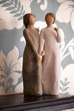 Wooden statue of two women holding hands, statue is on a black  Royalty Free Stock Images