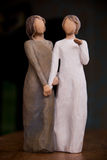 Wooden statue of two women holding hands, statue is on a black m stock photography