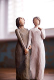 Wooden statue of two women holding hands, statue is on a black m Stock Photo
