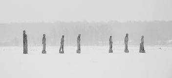 Wooden statues in snow Royalty Free Stock Images