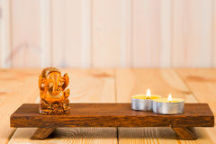 Wooden statuette of the god Ganesha and a candle Stock Photo