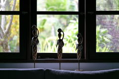 Wooden statuettes figurines, window view. Bali, Indonesia. Royalty Free Stock Photography