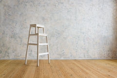 A wooden stepladder stands in a room with a white wall. Wooden staircase stands in a room with a white wall Stock Photos