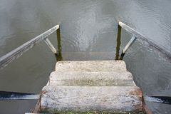 Wooden steps with handrails leading to the water with a reflection of the sky.  stock photo