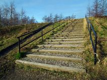 Wooden steps with railings. Wooden and gravel steps going up to a blue sky view Stock Photo