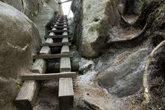 Wooden steps on rock face. Wooden steps leading up to open crack along rock face Royalty Free Stock Photos