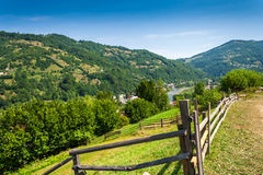 Wooden fence in mountains. Wooden stick fence in village in mountains with blue sky, green grass and path in good weather time Royalty Free Stock Photos