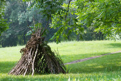Wooden stick house looking like indian hut,. Kids playing next to wooden stick house looking like indian hut, tepee Stock Image