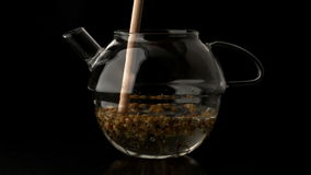 Wooden stick stirring teapot of water and loose tea stock video