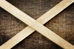 Wooden sticks crossed on old wooden. Background Stock Images