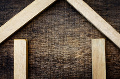 Wooden sticks forming a sketch house. On old wooden background Stock Photo