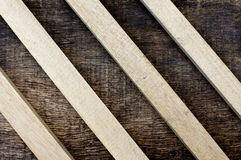 Wooden sticks on old wooden background. Parallel arrangement of wooden sticks on old wooden background Royalty Free Stock Image