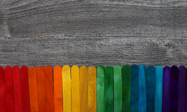 Wooden sticks painted in different colors on a wooden table. Wooden sticks painted in different colors on a grey wooden table stock images