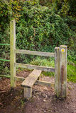Wooden Stile Along Footpath. An old wooden stile next to a gate along a public footpath Royalty Free Stock Image