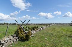 Wooden stile by a dry stone wall in spring season at the great plain grassland Alvaret at the swedish island Oland. Wooden stile by a dry stone wall in spring royalty free stock image