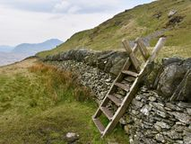 Wooden stile over stone wall stock photos