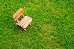 Wooden stool on green grass field Stock Photos