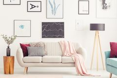 Posters in pastel living room. Wooden stool next to a beige couch with pink blanket against the wall with posters in pastel living room interior Stock Image