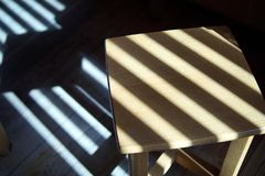 Wooden stool in the shadows of the blinds royalty free stock photography