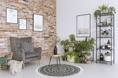 Relax room with grey armchair. Wooden stool with vase on round patterned carpet in relax room with grey armchair against brick wall vector illustration