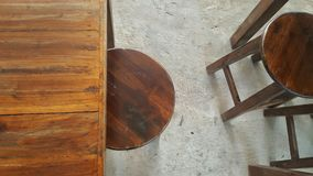 Wooden stools and desk on concrete plain floor Royalty Free Stock Images