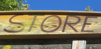 Wooden Store Sign on a happy summer day stock images