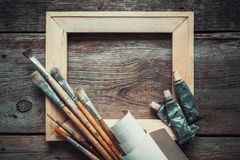 Wooden stretcher bar, paintbrushes, roll of artist canvas and paint tubes. Wooden stretcher bar, paintbrushes, roll of artist canvas and paint tubes on old stock photos