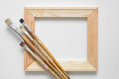 Wooden stretcher bar and paintbrushes on white artist canvas background. Top view. Copy space for text stock image