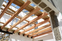 The wooden structure of the building. Installation of wooden beams at construction the roof truss system of the house. stock photography