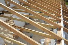 The wooden structure of the building. Wooden frame building. Wooden roof construction. Installation of wooden beams stock photos