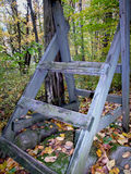 Wooden Structure In Forest. Deep within the forest a man-made wooden structure sits alone. The word is light and color and weathered. Orange colored leaves are Royalty Free Stock Photos