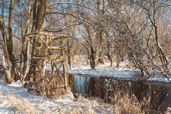 Wooden Structure on River Bank in Snowy Forest Stock Photography