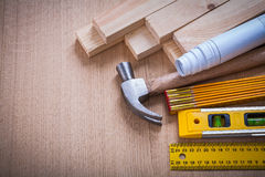 Wooden studs and meter ruler hammer blueprints Royalty Free Stock Image