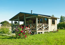 Wooden summer lodge with a flower bed Stock Photos