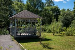Wooden summerhouse on lawn among lush green trees. On bright sunny summer day stock photo