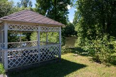 Wooden summerhouse on lawn among green trees. Wooden summerhouse standing on lawn among lush green trees in front of river on sunny summer day royalty free stock photography